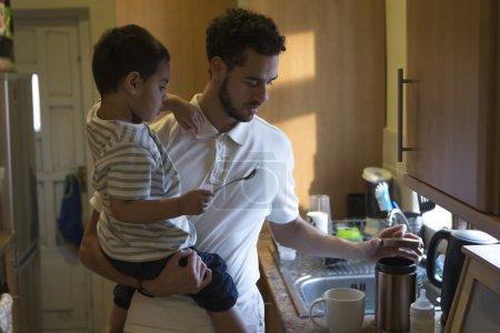 Photo pour Jeune papa faire une tasse de thé avec l'aide de son fils. Il ouvre un pot de sucre et le petit garçon tient la cuillère. - image libre de droit
