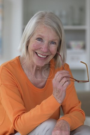 Photo for Portrait of a senior woman. She is sitting at a table with a pair of glasses in her hand whilst smiling and looking at the camera. - Royalty Free Image