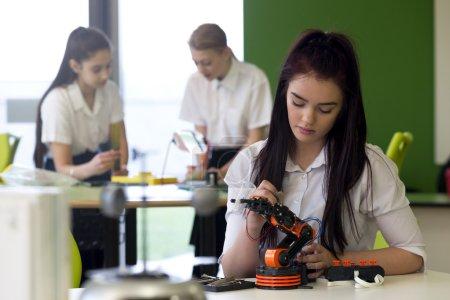 Photo pour Adolescente dans une leçon de design et de technologie. Elle construit un bras robotique et il y a d'autres étudiants qui travaillent en arrière-plan. . - image libre de droit