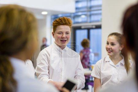 Photo pour Adolescent, parler à ses amis à l'école - image libre de droit
