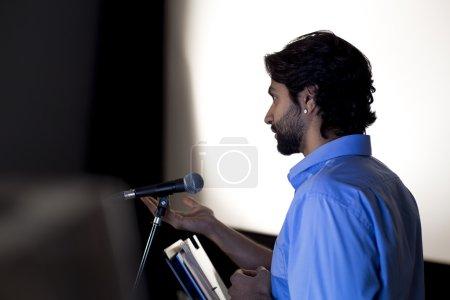 Photo pour Professeur masculin faisant un discours dans une salle de conférence. Il est debout sur le podium et sourit à la foule . - image libre de droit