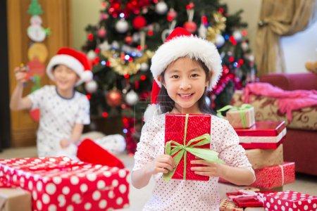 Photo pour Joyeux Chinois fille assise sur le sol dans son salon à la période de Noël. Elle est entourée de cadeaux, dont l'un qu'elle tient avec un grand sourire sur son visage. Son frère est en arrière-plan . - image libre de droit