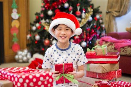 Photo pour Joyeux garçon chinois assis sur le sol dans son salon à la période de Noël. Il est entouré de cadeaux, dont l'un qu'il tient avec un grand sourire sur le visage . - image libre de droit