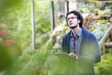 Photo pour Jeune homme utilisant une tablette numérique pour analyser les arbres . - image libre de droit