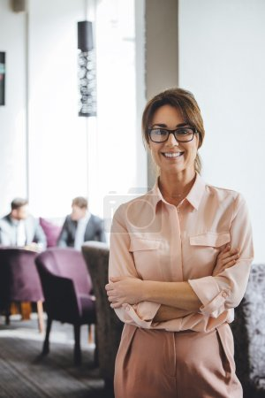 Photo for Business woman standing with her arms folded. She is smiling at the camera. Two men in suits can be seen talking in the background. - Royalty Free Image