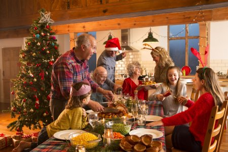Photo for A large family are all helping serve Christmas dinner. - Royalty Free Image