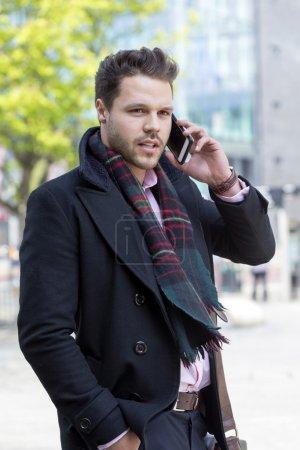 Photo pour Homme d'affaires dans la ville. Il est formellement habillé et parle à quelqu'un sur son smartphone. - image libre de droit