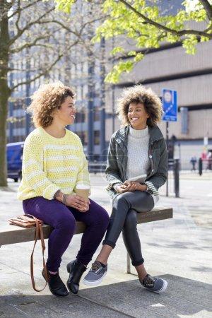 Photo pour Deux amis assis et parlant en ville. L'un boit du café et l'autre tient une tablette numérique . - image libre de droit