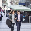 Couple in the city. They are walking arm in arm an...