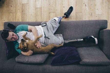 Photo pour Quadruple amputé de détente sur le canapé à la maison avec son chien. - image libre de droit