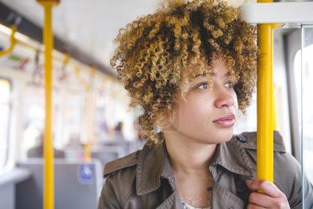 Photo pour Gros coup d'une femme au transport sur un train. Elle tient à la main courante et regarde par la fenêtre. - image libre de droit