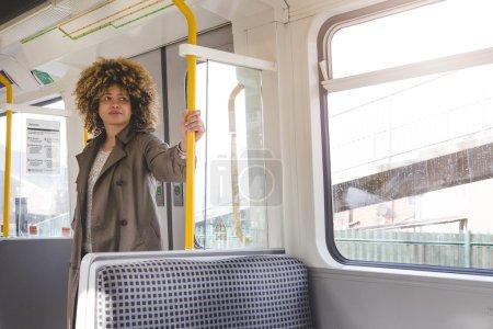 Photo pour Femme au transport pour travailler sur un train. Elle est debout et tenant à la poignée tout en regardant par la fenêtre. - image libre de droit