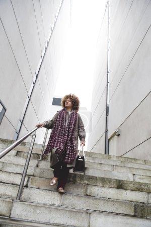 Photo pour Femme marchant dans un escalier de la ville. On dirait qu'elle vient de finir son travail et qu'elle a son sac à la main . - image libre de droit