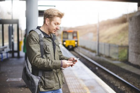 Photo pour Homme d'âge mûr avec un téléphone intelligent à une gare. Il s'apprête à monter dans un train qui tire en. - image libre de droit