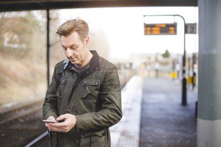 Photo pour Homme a une gare à l'aide de son smartphone pendant qu'il attend son train. - image libre de droit