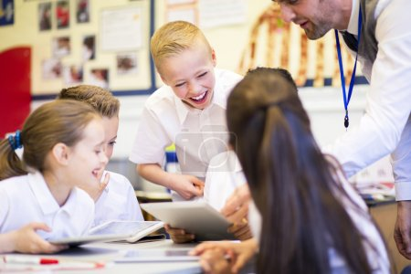 Photo for Happy students in classroom using a digital tablet, they are all wearing uniforms. - Royalty Free Image