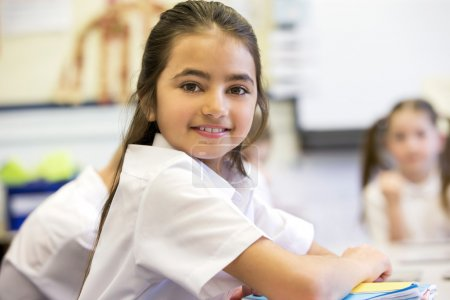 Photo for School girl smiles at the camera as she sits at her desk while working. - Royalty Free Image