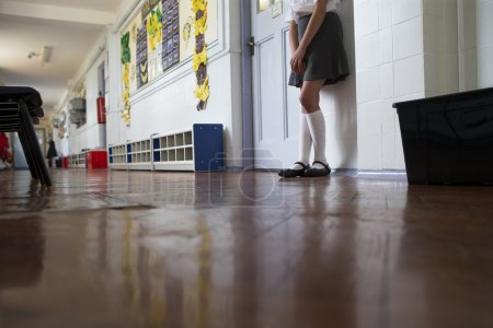 Naughty school girl stands in the corridor after b...