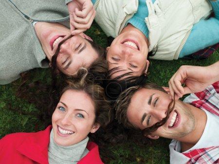 Photo pour Quatre amis s'étendant sur l'herbe avec leurs têtes ensemble. Les deux hommes utilisent l'une des filles long salaud pour imiter les moustaches. Ils sont tous souriants et regardant la caméra au-dessus d'eux. - image libre de droit