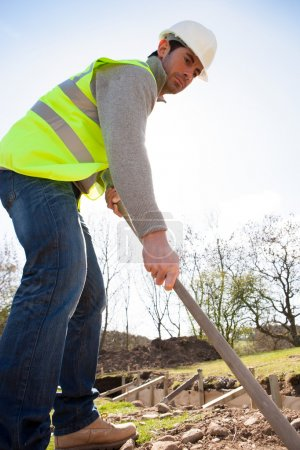 Male construction worker clearing ground to begin work