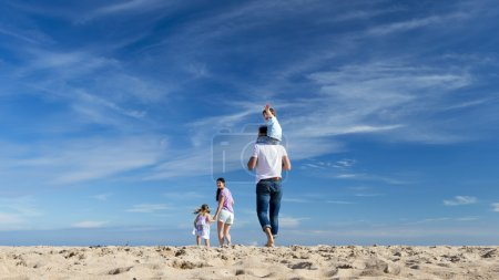 Photo for Family of four walking down to the coast. The little boy is on the fathers back and is waving at the camera. - Royalty Free Image