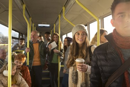 Photo pour Different people can be seen travelling on the bus. Some are talking to other people, others are using technology or looking out the window. - image libre de droit