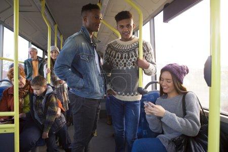Photo pour Deux hommes sont tiennent sur un bus. Il ya des gens autour d'eux parlant et en utilisant la technologie. - image libre de droit
