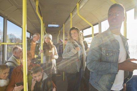 Photo pour Différentes personnes peuvent être vu en voyageant sur le bus. Certains parlent à d'autres personnes, d'autres sont à l'aide de la technologie ou de regarder par la fenêtre. - image libre de droit