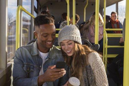 Photo pour Jeune couple sur un bus. Ils sont aussi bien regarder quelque chose sur un smartphone et souriant. Il ya des gens dans le fond, qui sont aussi dans le bus. - image libre de droit