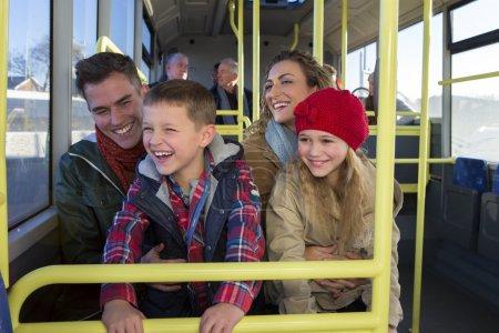 Photo pour Héhé sur le bus. Le chil ; dren sont assis sur les genoux de leurs parents et regarde par la fenêtre. Ils sont tous rire et sourire. - image libre de droit
