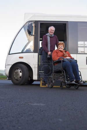 Elderly couple getting off their community bus