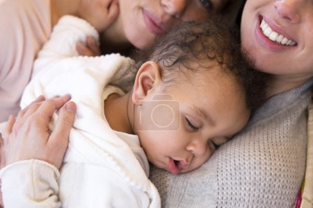 Photo for Same sex female couple lying down with their baby son - Royalty Free Image