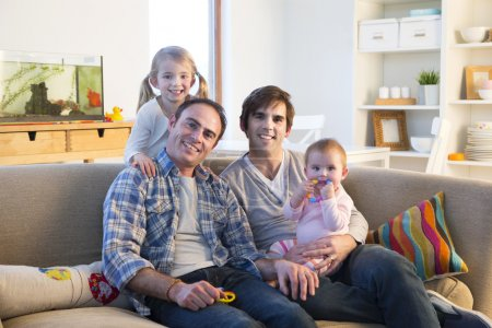 Male couple smiling for the camera with their daughters in their