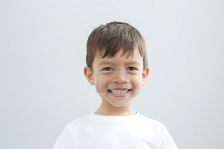Photo for Landscape head shot of a young boy on a plain background. He is smiling at the camera. - Royalty Free Image