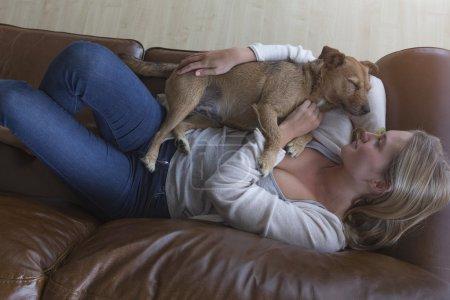 Mujer y perro acurrucándose en casa