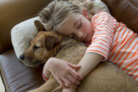 Photo pour Jeune fille câlinant son chien de compagnie sur un canapé à la maison . - image libre de droit