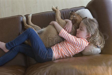 Young girl cuddling her pet dog at home