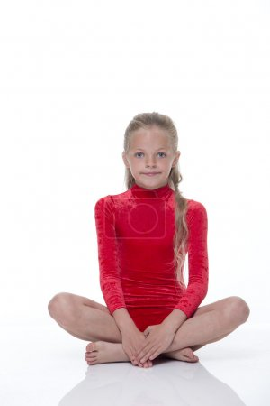 A young girl sitting on the floor crossed legged d...