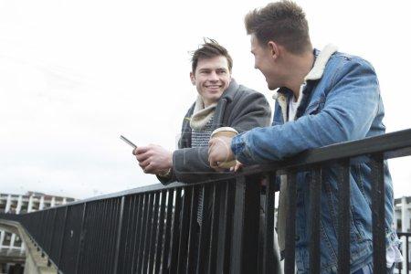 Photo pour Deux jeunes hommes parlant dans la ville. L'un tient un smartphone, l'autre tient une tasse à café jetable. - image libre de droit