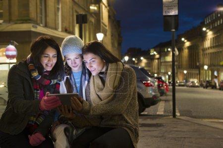 Photo pour Trois amis assis dans la ville regardant une tablette numérique le soir . - image libre de droit