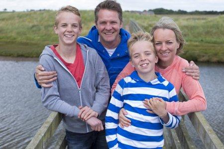 Photo pour Happy Family of Four debout sur un pont au-dessus de l'eau. Ils ont leurs bras autour de l'autre et sourient à la caméra - image libre de droit