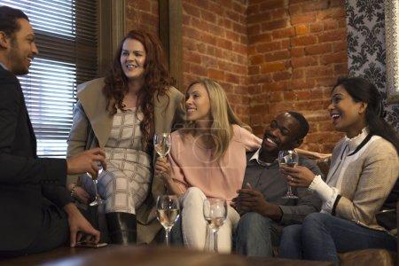 Photo pour Petit groupe d'amis assis dans un bar, dégustant quelques verres tout en bavardant ensemble . - image libre de droit