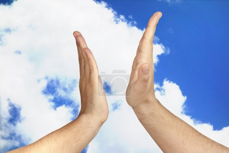 Hands giving a High Five outdoor against blue sky clouds