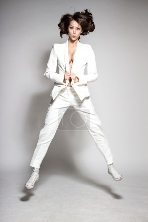 Awesome caucasian attractive joyful happy sexy dance model is jumping in studio wearing white suit on gray background