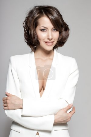 Portrait of gorgeous young caucasian attractive sexy business woman or secretary wearing white suit