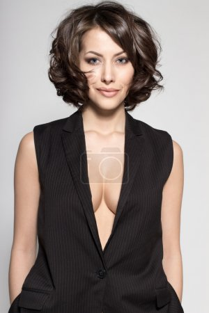 Portrait of gorgeous young caucasian attractive sexy business woman or secretary wearing black jacket without sleeves