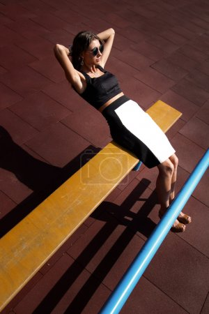 Young sporty teenage model pumps and crunches the abdominals and posing on playground near horizontal and parallel bars, stairs, wearing black and white top and skirt