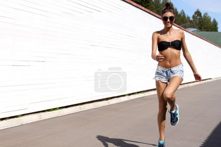 Young European teenage brunette sports model running outdoors along white wooden wall, jumping, jogging, wearing blue jeans mini shorts, sneakers, round sunglasses and black swimwear top