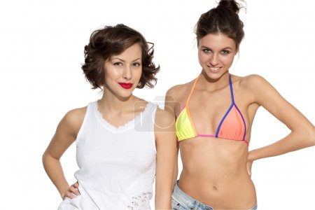 Two girls looking with expressive emotion, exited, shocked, happy, surprised, young beautiful caucasian female brunette models in shirt, jeans shorts, swimwear on white isolated background