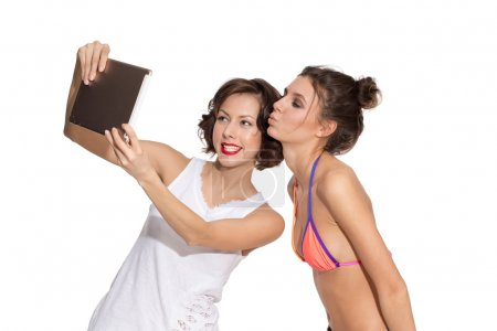 Young beautiful caucasian female brunette models in white t-shirt and swimsuit bikini posing with expressive emotion, grimacing, making selfie, exited, happy, surprised holding, looking at tablet pc isolated on white